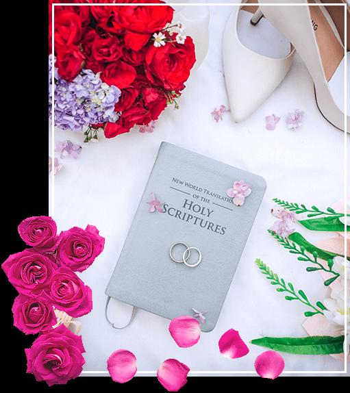 Kwiaty, róże i dzienniczek weselny wraz z obrączkami i szpilkami na jedwabnej tkaninie